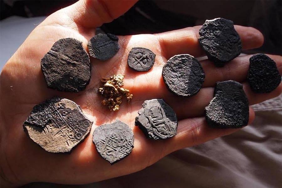 """Moedas e pó de ouro encontrados no Whydah Gally, navio capturado pelo pirata Samuel """"Black Sam"""" Bellamy"""