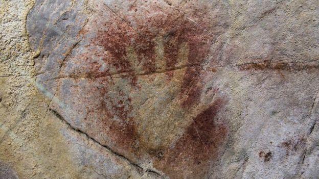 Na parede da gruta El Castillo, na Espanha, o contorno de uma mão feito com tinta vermelha