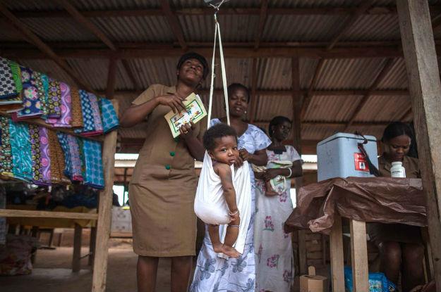 Trabalhor de saúde comunitária pesa bebês após vaciná-los. Em 2012, o Gana se tornou o primeiro país na África a introduzir simultaneamente vacinas contra doenças pneumocócicas e rotavírus.