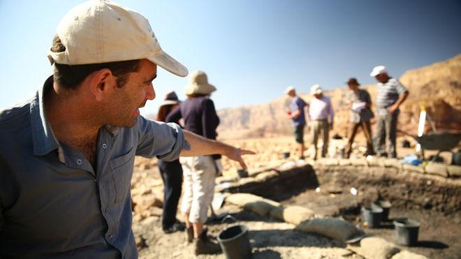 O arqueólogo Erez Ben-Yosef aponta para o local das escavações
