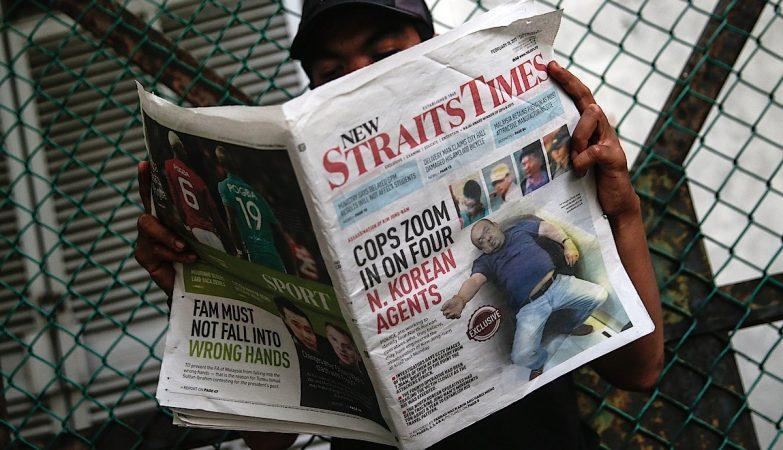 Homem na Malásia lendo o jornal Strait Times de 18 de fevereiro. Na capa, Kim Jong Nam após ser envenenado