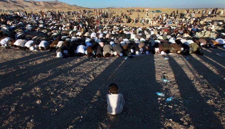 Menino refugiado observa orações