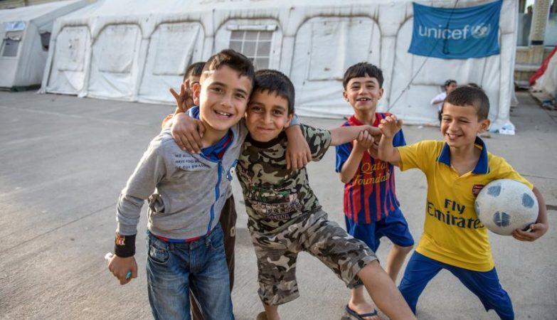 Crianças param jogo de futebol para posarem para a foto em campo de refugiados