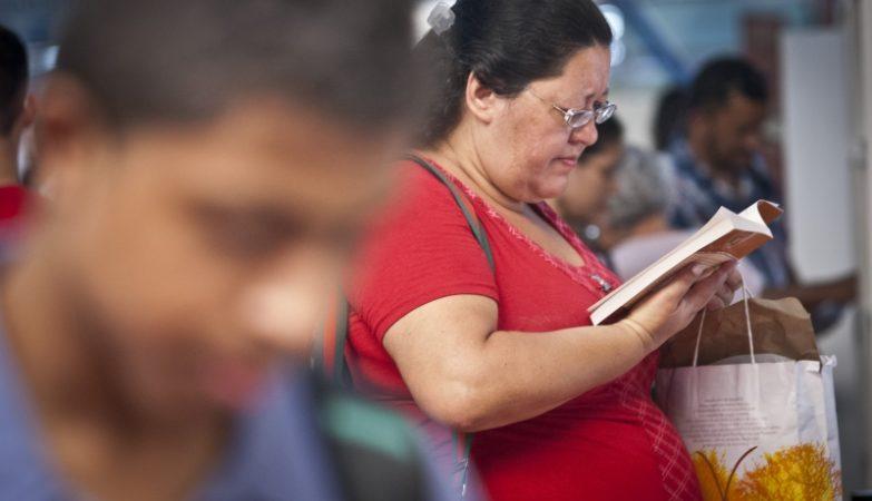 Mulher gorda talvez obesa a ler na feira do livro do metro em São Paulo