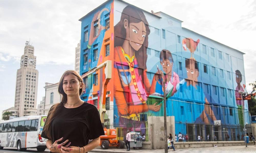 Luna Buschinelli ao lado de sua obra no Rio de Janeiro